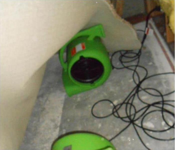 Our drying equipment drying a floor damaged by flood watera slink disaster caused by a leak in this basement