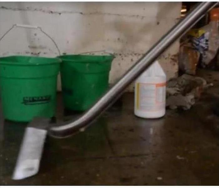 SERVPRO cleaning supplies and water extractor on water damaged floor