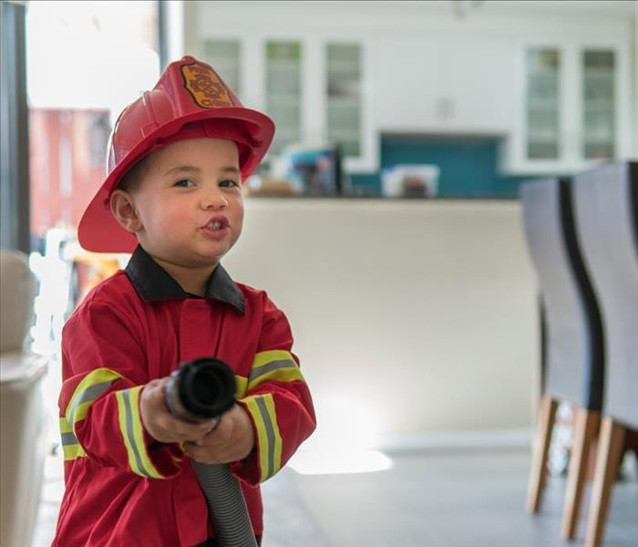 Little Boy dressed up as a firefighter and pointing a fire hose
